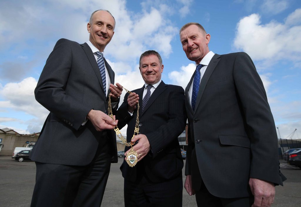 The Institute of Directors Northern Ireland (IoD NI) has appointed Gordon Milligan as its new Chairman. He is pictured, centre, accepting the chain of office from outgoing Chairman Ian Sheppard, at the premises of construction firm Henry Brothers, alongside David Henry, Managing Director of Henry Brothers. Mr Milligan, who is Deputy Chief Executive of Translink, said he planned to put member engagement at the top of his agenda.