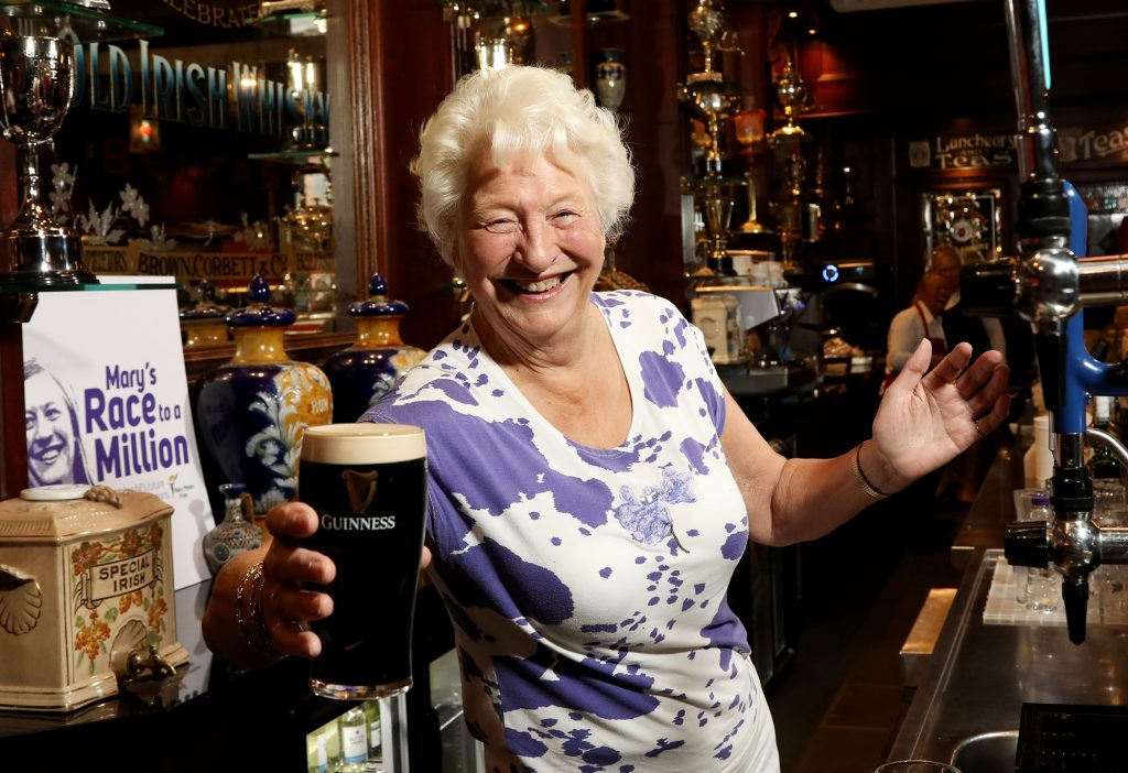 Dame Mary Peters CH, DBE celebrates ticking 'pulling a pint' off her bucket list in the Dark Horse, Belfast to launch the final push towards 'Mary's Race to a Million.'