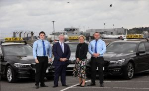 Christopher McCausland and Katy Best stand in front of two Value Cabs cars along with two drivers.